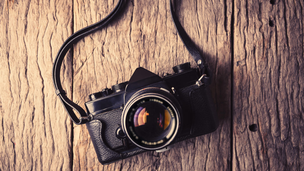 Retro camera on wood table background vintage color tone. Retro camera. Retro camera vintage. Retro camera on table. Retro camera classic. Retro camera background concept. Retro camera  photography